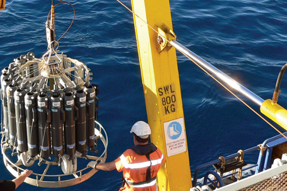 Two men deploying a CTD instrument from the back of a research ship