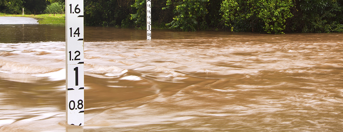 Brown flood water over a road with flood depth indicators