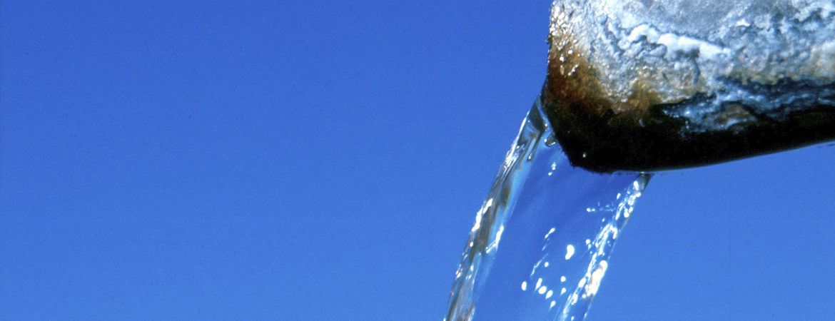 Water pouring out of a metal pipe against a blue sky background