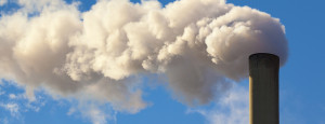 Clouds billowing from a factory smokestack against a blue sky background