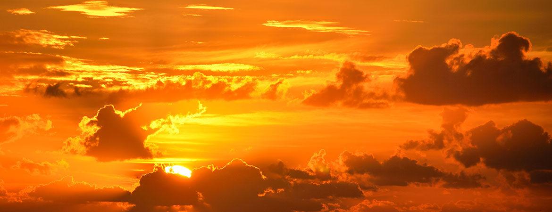 Sun in an orange sky behind clouds