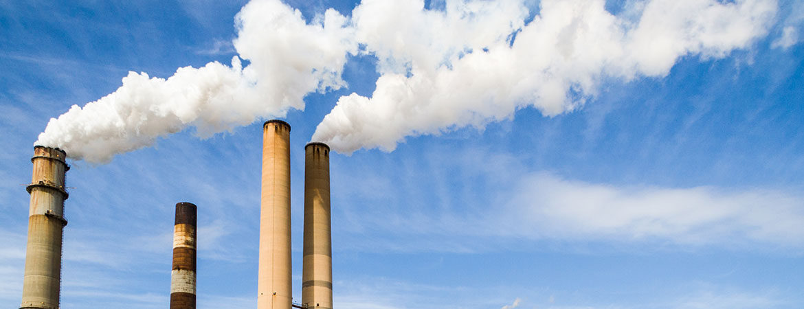 Four smokestacks billowing smoke against a blue sky