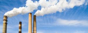 Four smokestacks billowing smoke against a blue sky