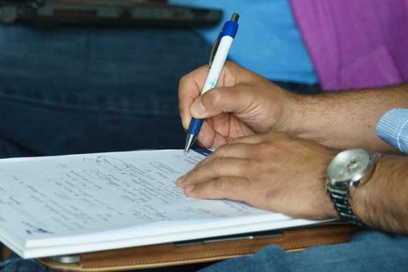 Man's hand writing on a notepad