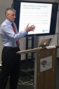 A man at a lectern with a PowerPoint presentation in the background