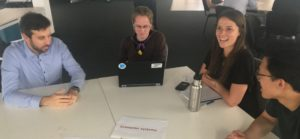 Four people sitting around a desk talking